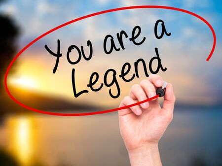 Man Hand writing You are a Legend with black marker on visual screen. Isolated on background. Business, technology, internet concept. Stock Photo