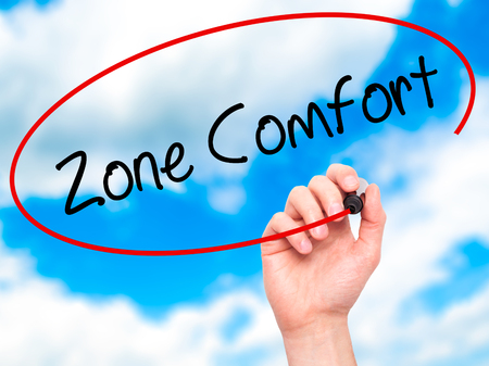 quo: Man Hand writing Zone Comfort with black marker on visual screen. Isolated on sky. Business,  internet concept. Stock Photo