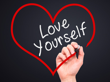 egoistic: Man Hand writing Love Yourself with marker on transparent wipe board, inside heart shape. Isolated on black. Business, internet, technology concept. Stock Photo
