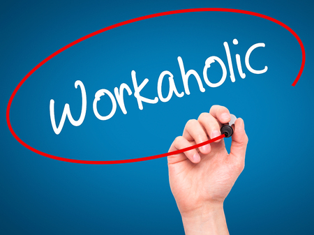 workaholic: Man Hand writing Workaholic with black marker on visual screen. Isolated on blue. Business, technology, internet concept.