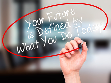 defined: Man Hand writing Your Future is Defined by What You Do Today with black marker on visual screen. Isolated on office. Business, technology, internet concept. Stock Image