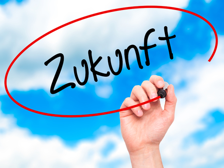 global retirement: Man Hand writing Zukunft (Future in German)  with black marker on visual screen. Isolated on background. Business, technology, internet concept. Stock Photo