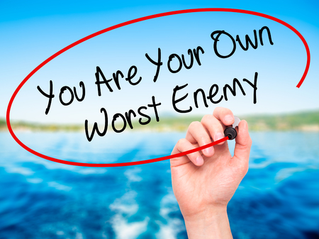 worst: Man Hand writing You Are Your Own Worst Enemy with black marker on visual screen. Isolated on background. Business, technology, internet concept. Stock Photo