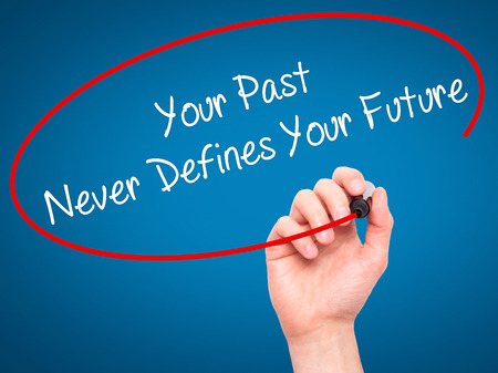 defines: Man Hand writing Your Past Never Defines Your Future with black marker on visual screen. Isolated on blue. Business, technology, internet concept. Stock Photo Stock Photo