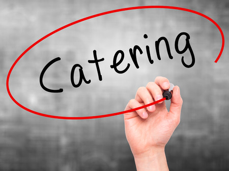 cuisine entertainment: Man Hand writing Catering with marker on transparent wipe board. Isolated on grey. Business, internet, technology concept.  Stock Photo Stock Photo