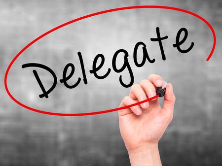 delegar: Hombre de la mano escribiendo Delegado marcador negro en la pantalla visual. Aislado en gris. Negocios, la tecnología, el concepto de internet. imagen de archivo