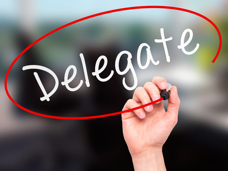 designate: Man Hand writing Delegate black marker on visual screen. Isolated on office. Business, technology, internet concept. Stock Image