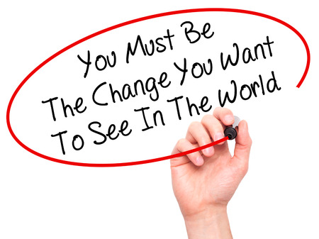 be the change: Man Hand writing You Must Be The Change You Want To See In The World with black marker on visual screen. Isolated on white. Business, technology, internet concept. Stock Photo
