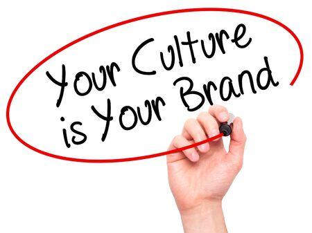 Hombre de la mano de escribir su cultura es su marca con un marcador negro en la pantalla visual. Aislado en blanco. Negocios, la tecnología, el concepto de internet. Foto de stock