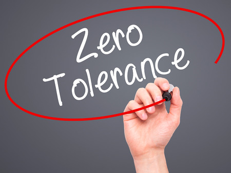 tolerance: Man Hand writing Zero Tolerance with black marker on visual screen. Isolated on background. Business, technology, internet concept. Stock Photo