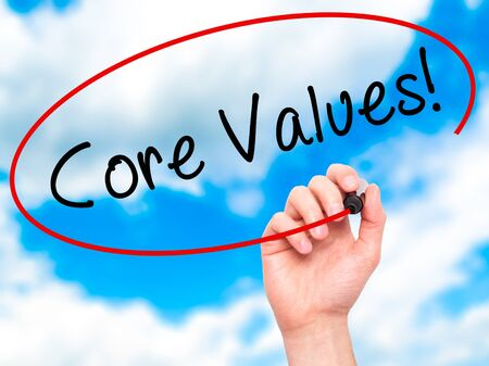scruples: Man Hand writing Core Values with marker on transparent wipe board. Isolated on sky. Business, internet, technology concept. Stock Photo