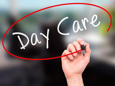day care center: Man Hand writing Day Care with marker on transparent wipe board isolated on office. Business, internet, technology concept. Stock Photo