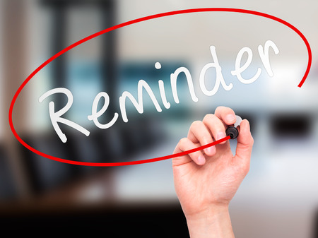 dea: Man Hand writing Reminder with marker on transparent wipe board. Isolated on office. Business, internet, technology concept. Stock Photo