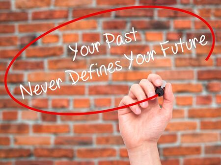 defines: Man Hand writing Your Past Never Defines Your Future with black marker on visual screen. Isolated on bricks. Business, technology, internet concept. Stock Photo Stock Photo