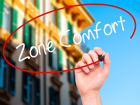 quo: Man Hand writing Zone Comfort with black marker on visual screen. Isolated on city. Business,  internet concept. Stock Photo Stock Photo