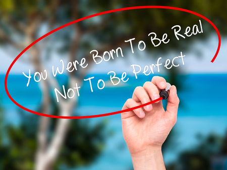 true born: Man Hand writing You Were Born To Be Real Not To Be Perfect with black marker on visual screen. Isolated on nature. Business, technology, internet concept.
