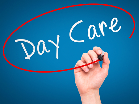 day care center: Man Hand writing Day Care with marker on transparent wipe board isolated on blue. Business, internet, technology concept. Stock Photo Stock Photo
