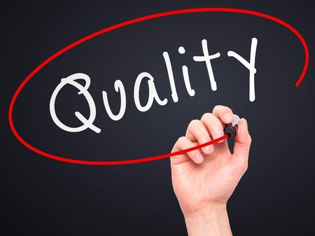 Man Hand schreiben Qualität mit Marker auf transparente Platte wischen. Isoliert auf schwarz. Geschäft, Internet, Technologie-Konzept. Stockfoto
