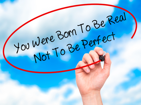 rightful: Man Hand writing You Were Born To Be Real Not To Be Perfect with black marker on visual screen. Isolated on sky. Business, technology, internet concept. Stock Photo