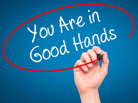 best ad: Man Hand writing You Are in Good Hands with black marker on visual screen. Isolated on blue. Business, technology, internet concept. Stock Photo