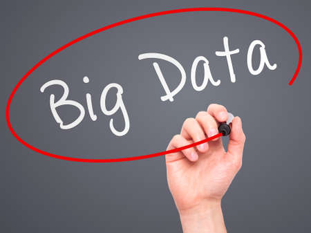 Man Hand writing Big Data with marker on transparent wipe board. Isolated on grey. Business, internet, technology concept. Stock Photo