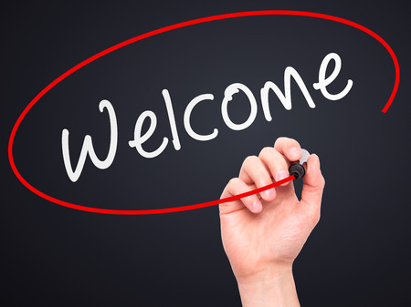 usher: Man Hand writing Welcome with marker on transparent wipe board. Isolated on black. Business, internet, technology concept. Stock Photo