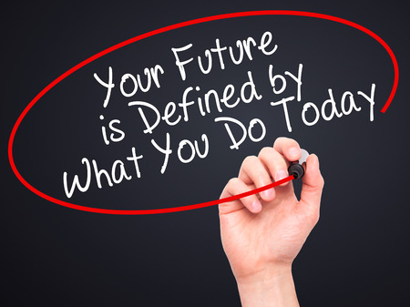 defined: Man Hand writing Your Future is Defined by What You Do Today with black marker on visual screen. Isolated on black. Business, technology, internet concept. Stock Image Stock Photo