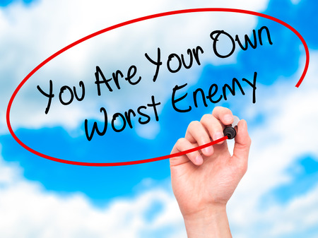 enemy: Man Hand writing You Are Your Own Worst Enemy with black marker on visual screen. Isolated on background. Business, technology, internet concept. Stock Photo