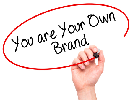 Man Hand Writing Vous êtes votre propre marque avec un marqueur noir sur l'écran visuel. Isolé sur blanc Affaires, technologie, concept internet. Photo Banque d'images