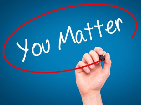 business matter: Man Hand writing You Matter with black marker on visual screen. Isolated on blue. Business, technology, internet concept. Stock Photo