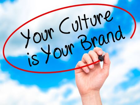 identidad cultural: Man Hand writing Your Culture is Your Brand with black marker on visual screen. Isolated on sky. Business, technology, internet concept. Stock Photo