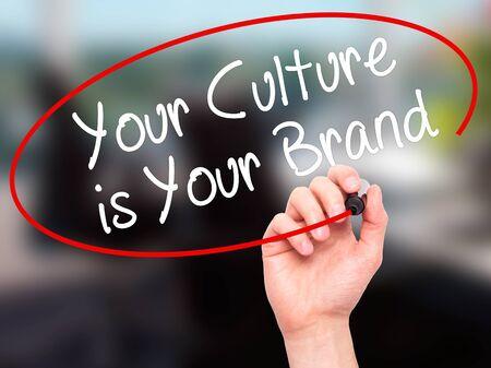 identidad cultural: Hombre de la mano de escribir su cultura es su marca con un marcador negro en la pantalla visual. Aislado en la oficina. Negocios, la tecnología, el concepto de internet. Foto de stock