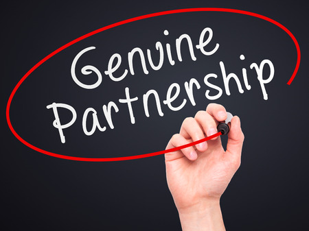 legitimate: Man Hand writing Genuine Partnership with marker on transparent wipe board. Isolated on black. Business, internet, technology concept. Stock Photo