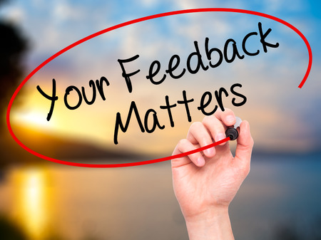 Man Hand writing Your Feedback Matters with black marker on visual screen. Isolated on nature. Business, technology, internet concept. Stock Photo Stock Photo