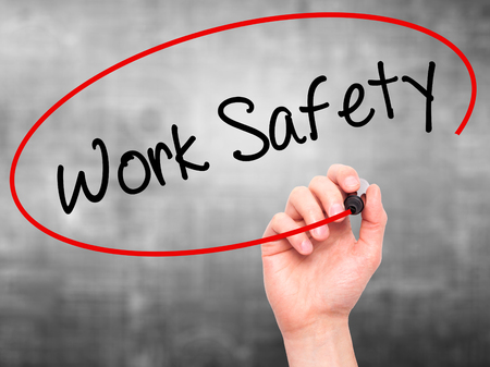 work safety: Man Hand writing Work Safety with black marker on visual screen. Isolated on grey. Business, technology, internet concept. Stock Photo