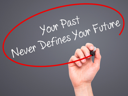 defines: Man Hand writing Your Past Never Defines Your Future with black marker on visual screen. Isolated on grey. Business, technology, internet concept. Stock Photo