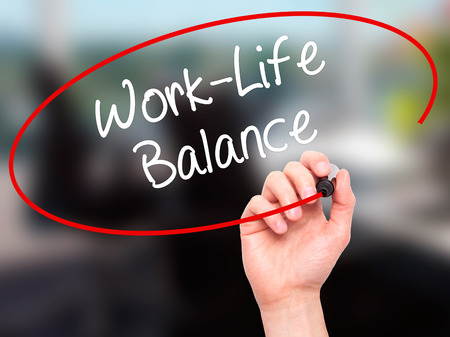 health equity: Man Hand writing Work-Life Balance with black marker on visual screen. Isolated on office. Business, technology, internet concept. Stock Photo
