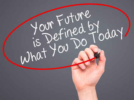 defined: Man Hand writing Your Future is Defined by What You Do Today with black marker on visual screen. Isolated on grey. Business, technology, internet concept. Stock Image