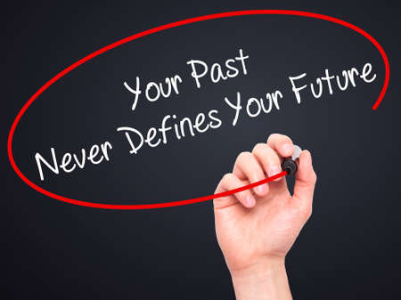 defines: Man Hand writing Your Past Never Defines Your Future with black marker on visual screen. Isolated on black. Business, technology, internet concept. Stock Photo Stock Photo