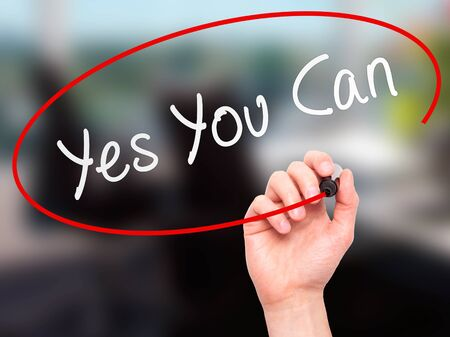 tu puedes: Man Hand writing Yes You Can with marker on transparent wipe board. Isolated on office. Business, internet, technology concept.  Stock Photo