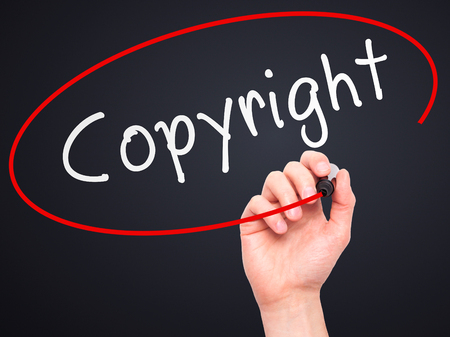 plagiarism: Man hand writing Copyright on visual screen. Business,help, internet, technology concept. Isolated on black. Stock Photo