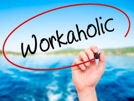 workaholic: Man Hand writing Workaholic with black marker on visual screen. Isolated on nature. Business, technology, internet concept. Stock Photo