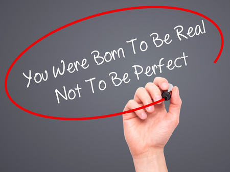true born: Man Hand writing You Were Born To Be Real Not To Be Perfect with black marker on visual screen. Isolated on grey. Business, technology, internet concept.