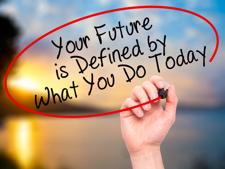 Man Hand writing Your Future is Defined by What You Do Today with black marker on visual screen. Isolated on nature. Business, technology, internet concept. Stock Image