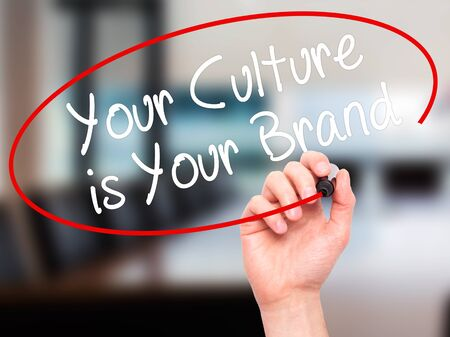 identidad cultural: Man Hand writing Your Culture is Your Brand with black marker on visual screen. Isolated on office. Business, technology, internet concept. Stock Photo