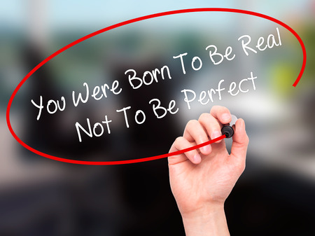 rightful: Man Hand writing You Were Born To Be Real Not To Be Perfect with black marker on visual screen. Isolated on office. Business, technology, internet concept.