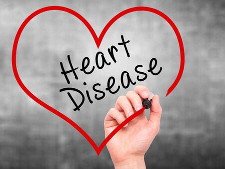 tachycardia: Man Hand writing Heart Disease with marker on transparent wipe board. Isolated on grey. Health, internet, technology concept. Stock Photo
