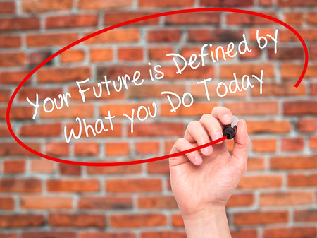 defined: Man Hand writing Your Future is Defined by What you Do Today  with black marker on visual screen. Isolated on bricks. Business, technology, internet concept. Stock Photo