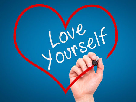 egoistic: Man Hand writing Love Yourself with marker on transparent wipe board, inside heart shape. Isolated on blue. Business, internet, technology concept. Stock Photo