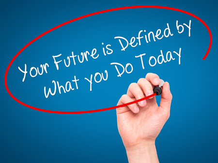 defined: Man Hand writing Your Future is Defined by What you Do Today  with black marker on visual screen. Isolated on blue. Business, technology, internet concept. Stock Photo